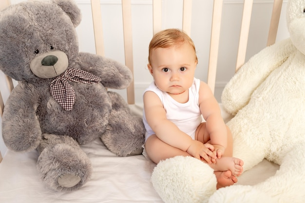 大きなテディベアとベビーベッドに座っている1歳の男の子、保育園で赤ちゃん