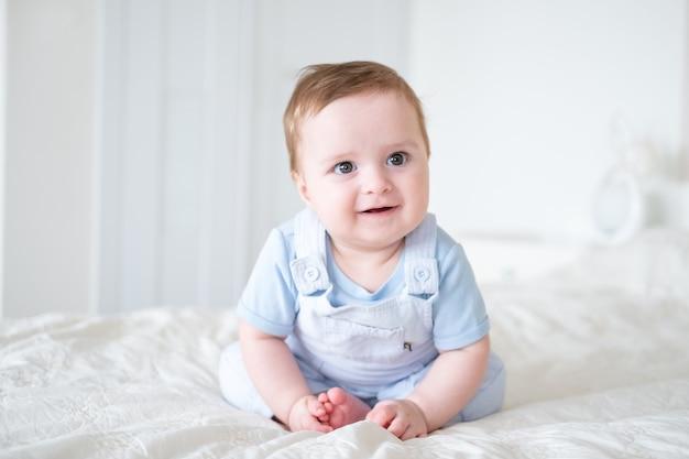 Мальчик 6 месяцев в голубой одежде улыбается и сидит на белой кровати дома