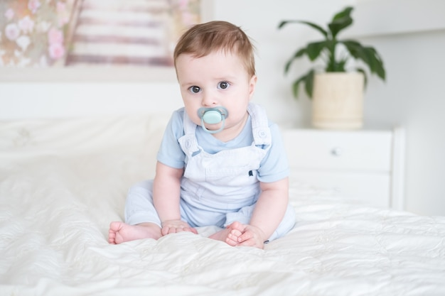 Baby boy 6 months old with nipple in blu clothes and sitting on white bed at home.
