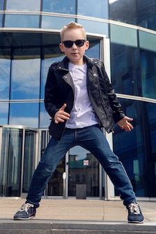 Baby boy 7 - 8 years in a black leather jacket dancing in the street