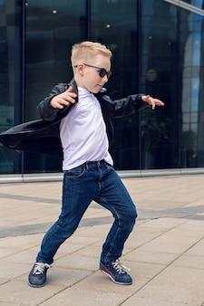 Мальчик 7-8 лет в черной кожаной куртке танцует на улице