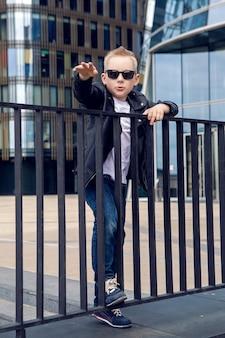 サングラスと黒い革のジャケットの笑顔で7-8歳の男の子