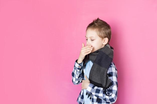Малыш, мальчик 8-9 лет на розовом фоне болен коронавирусом расстроен, держит градусник