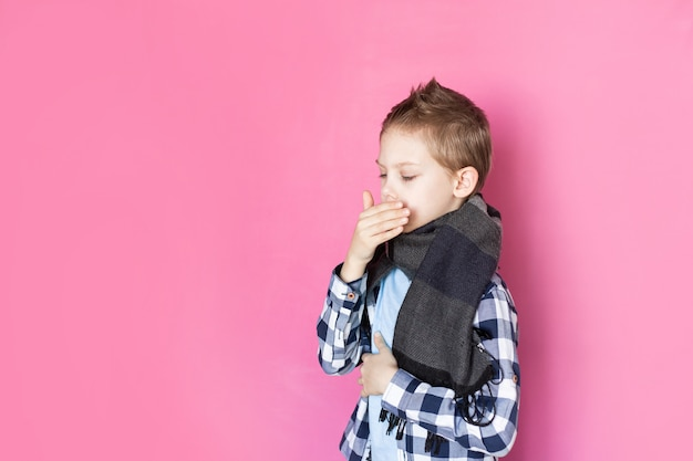 Baby, boy 8-9 years old on pink background sick with coronavirus upset, holds a thermometer