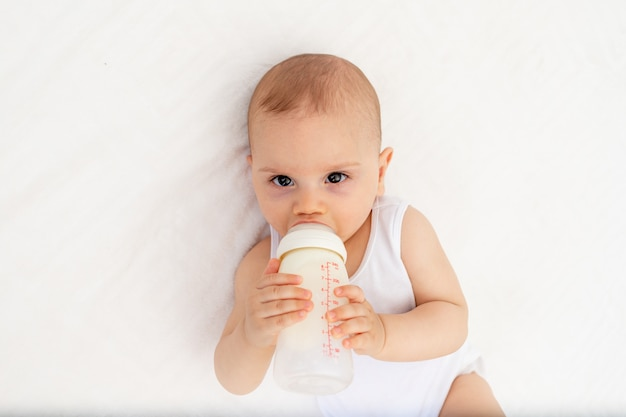 Baby boy 8 months old lies drinking milk from a bottle on the bed in the nursery, feeding the baby, baby food concept