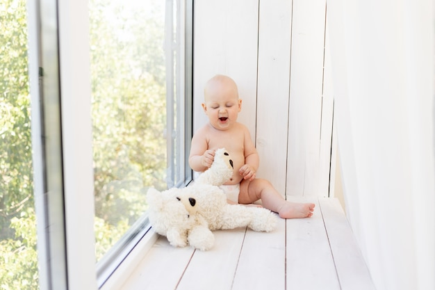 Baby boy 8 months old lying in diapers on a white bed with a bottle of milk at home legs up, top view, baby food concept, baby drinking water from a bottle