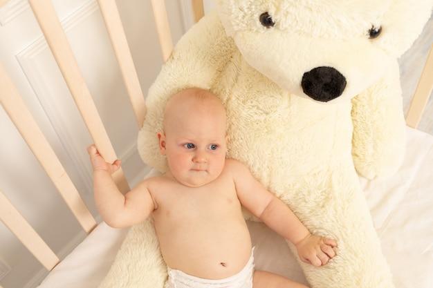 保育園で大きなテディベアとベビーベッドでおむつに座っている男の子8ヶ月