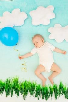 Мальчик среди облаков с воздушным шаром спит