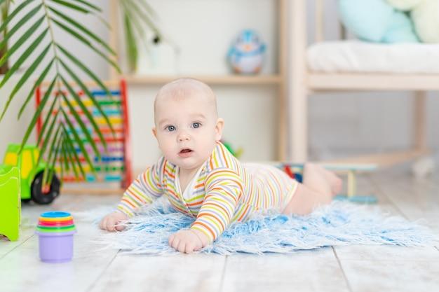 어린이 방에있는 장난감 중 아기, 바닥에서 노는 귀여운 재미있는 웃는 작은 아기, 어린이 발달 및 게임의 개념