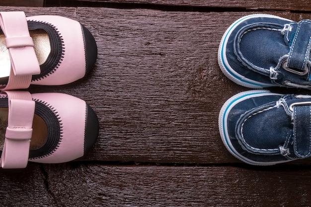 木製の背景に男の子と女の子の靴。子供の靴。上面図。