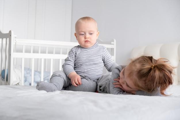 Мальчик и маленькая девочка сестра весело дома на кровати. домашние занятия для детей.