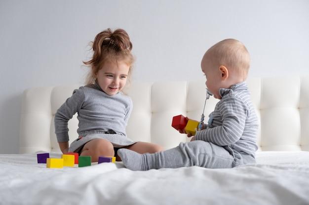 ベッドの上で家で木のおもちゃを遊んでいる男の子と妹。子供のためのホームアクティビティ。