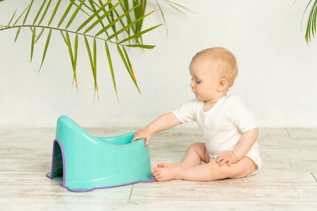 집 바닥에 파란색 냄비와 흰색 바디 수트에 아기 소년 금발