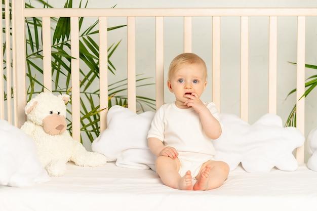 Мальчик блондинка с голубыми глазами в белом боди на кровати с хлопковым нижним бельем дома перед сном