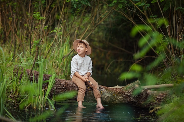 Baby boy boy in rustic clothes and wicker hat sits with a fishing rod in his hands and catches fish on a log across the river. hobbies and leisure for men.