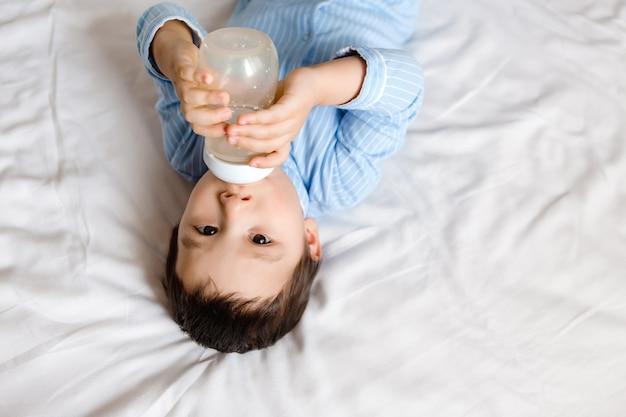 男の子のブルネットはブルーのパジャマでベッドの上にあり、ボトルから牛乳を飲みます。ベビーフード