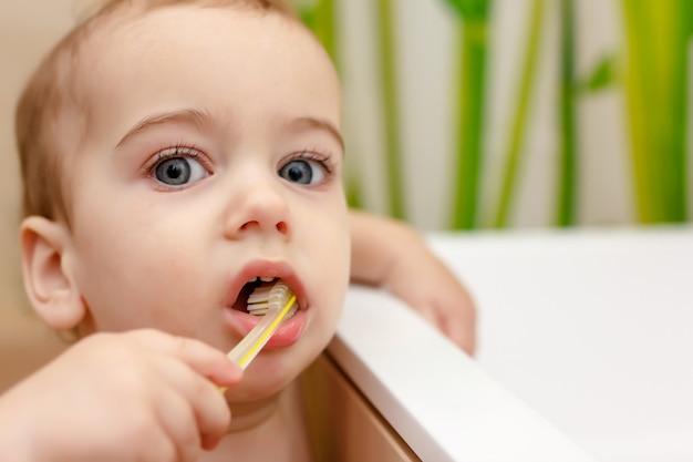 Baby boy brushes teeth in bathroom. concept of oral hygiene.