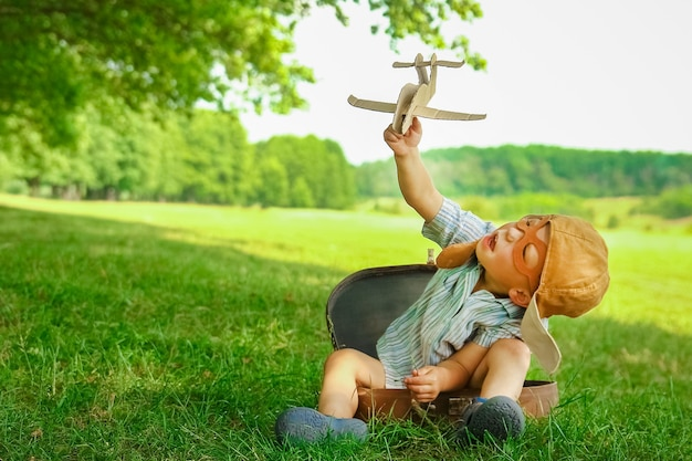 A baby boy by the plane plays on nature in the park. boy on vacation pilot.