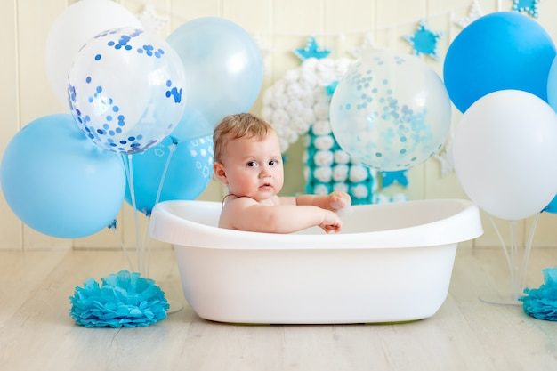 Baby boy celebrates birthday 1 year in a bath with balloons, bathing baby with blue balloons