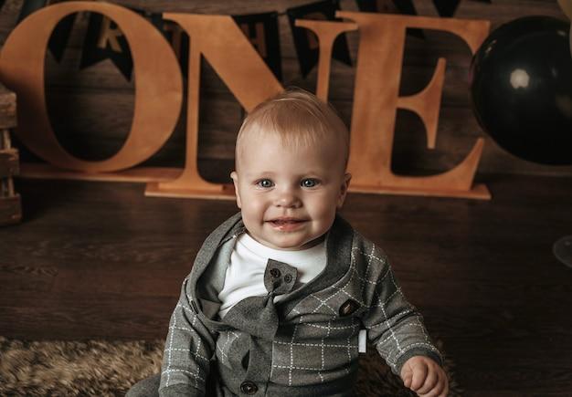 Мальчик празднует свой первый год на коричневом фоне
