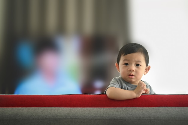 Baby boy climbing on sofa in living room at home.