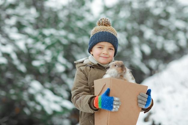 Baby boy крупным планом держит коробку с кроликом в руках