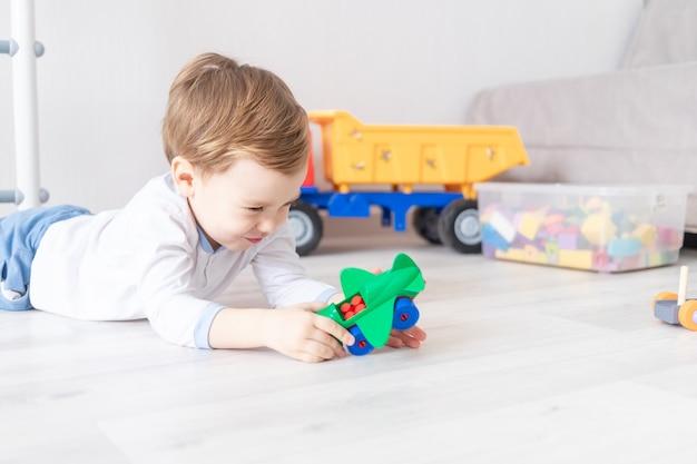 아기는 아이의 게임의 개념 인 집 바닥에 비행기 생성자를 수집합니다.