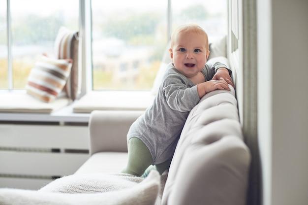 Мальчик ползет и залезает на диван против большого окна