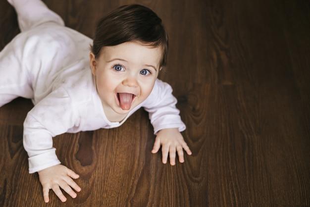 나무 바닥에 크롤 링하는 아기