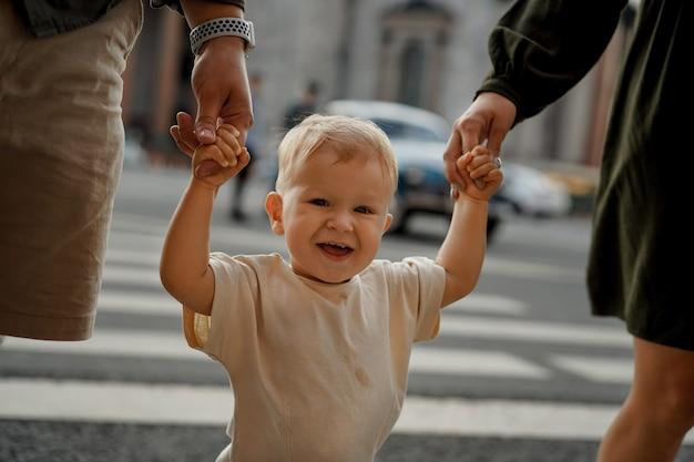 ロシアのサンクトペテルブルク市で両親を手に持って横断歩道で道路を横断する男の子。セレクティブフォーカスの画像。高品質の写真