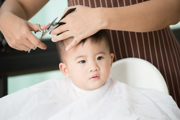 Baby boy cutting hair by his mom at home