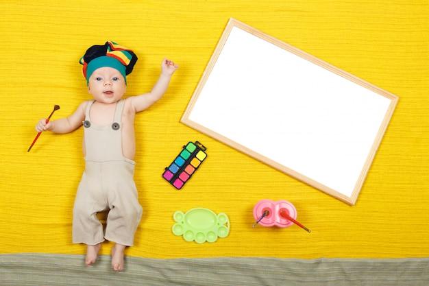 Baby мальчик рисовать с цветными карандашами. ребенок лежал