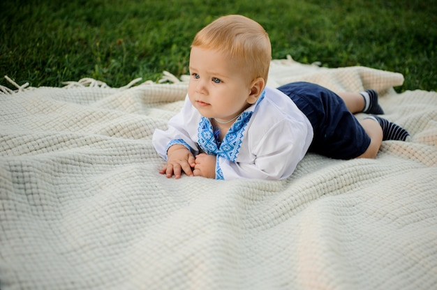 Baby boy dressed in the embroidered shirt lying on the plaid on the green grass