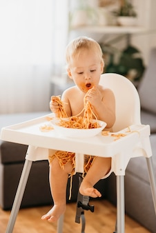 Baby boy eating pasta in his highchair