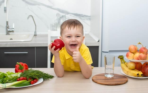 Мальчик ест здоровую пищу, показывая жест пальца вверх. маленький мальчик любит есть овощи. концепция здорового питания.