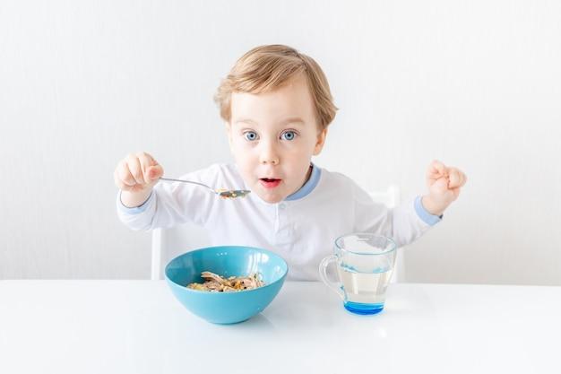 Мальчик ест ложкой дома концепция еды и питания для детей