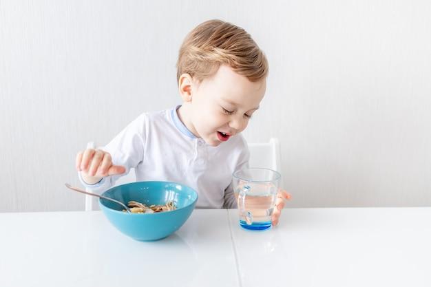 Мальчик ест ложкой дома, концепция питания и питания для детей