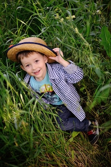 Baby boy in the hat playing in the grass
