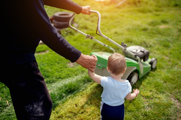 Baby boy and his father mowing the grass with lawnmower.