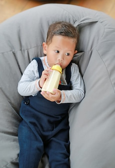 Baby boy holding and feeding milk from bottle lying on sofa.
