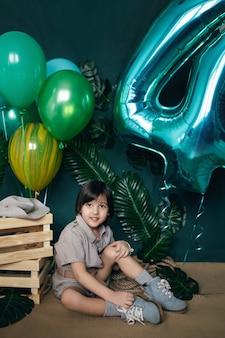 男の子は彼の誕生日に緑の背景に家で風船を持っています