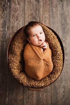 茶色のラップを着た男の子が新生児にあくびをしている