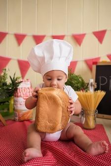 Мальчик в шляпе шеф-повара ест хлеб на деревянной стене