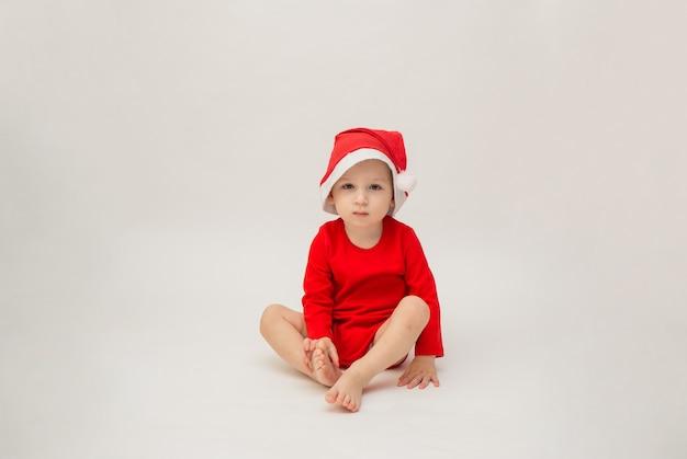 Мальчик в новогодней шапке на белой изолированной стене