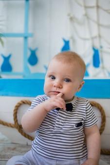 줄무늬 죄수 복을 입은 아기가 입에 손가락을 쥐고있다.