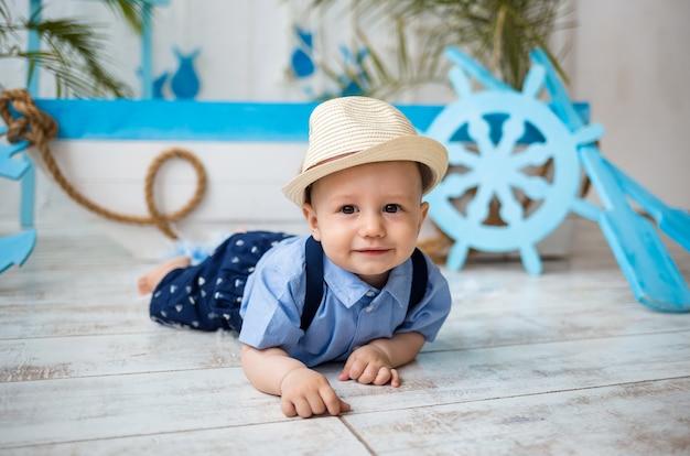Мальчик в костюме и соломенной шляпе лежит на деревянном полу на поверхности с морским декором