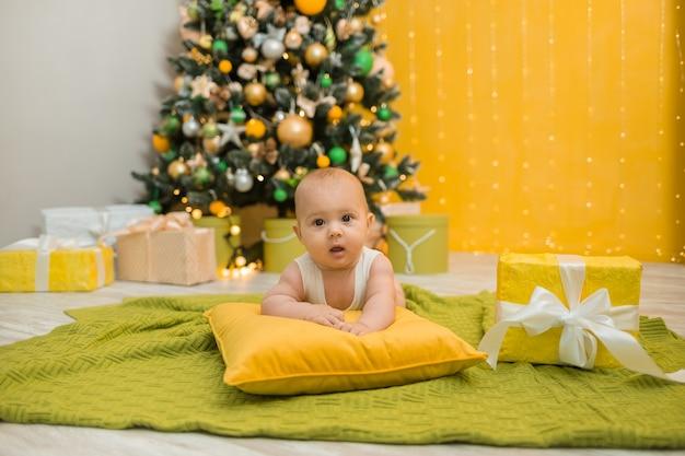 Мальчик в белом боди лежит на зеленом одеяле с подарком с елкой