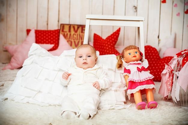 白いエレガントなスーツを着た男の子がピンクのドレスを着たヴィンテージ人形の隣に座っています