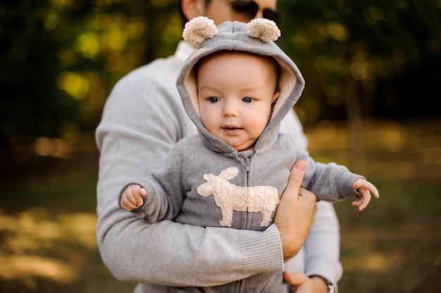 아빠 야외의 손에 재미있는 옷을 입고 아기