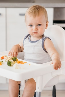 台所で野菜を食べるハイチェアの男の子
